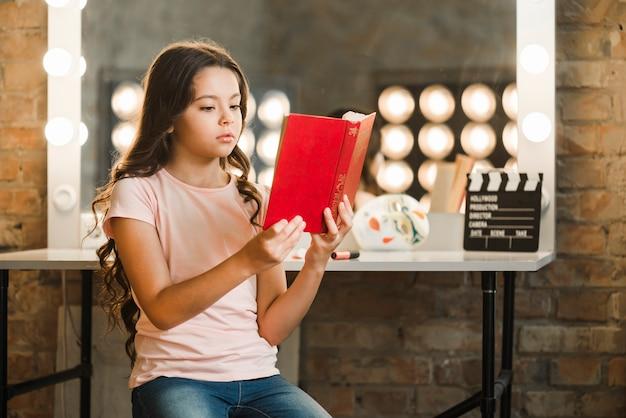 Jolie fille assise devant un livre de lecture miroir