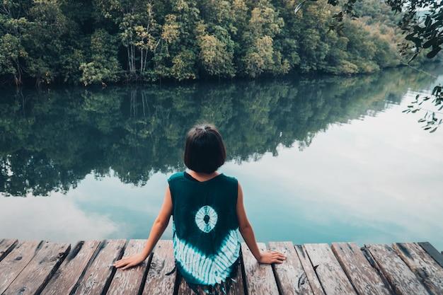 Jolie fille assise sur la planche de bois se reposer et regarder sur la rivière