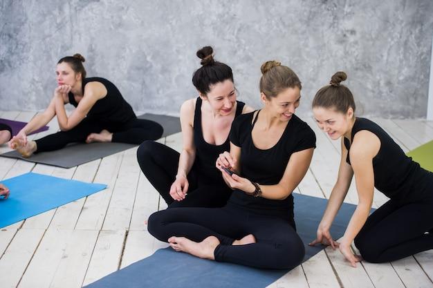 Jolie fille assise et socialiser avec le groupe après leur cours de yoga