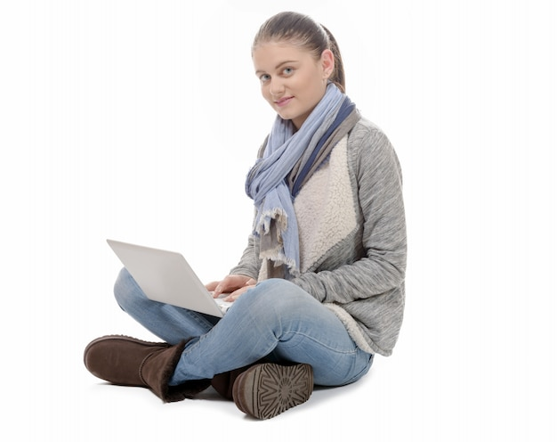Jolie fille assise en tailleur avec un ordinateur portable sur les genoux