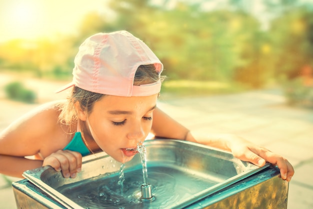 Jolie fille assoiffée boit de l'eau de l'évier