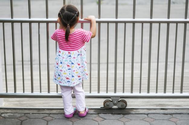 Jolie fille attend les parents à la porte de la maison