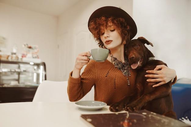 Jolie fille au chapeau boit du café dans un café respectueux des animaux