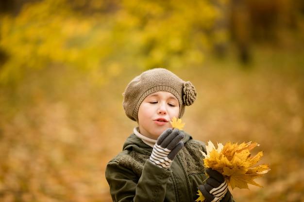 Jolie fille au chapeau vert et manteau à feuilles jaunes dans le parc en automne