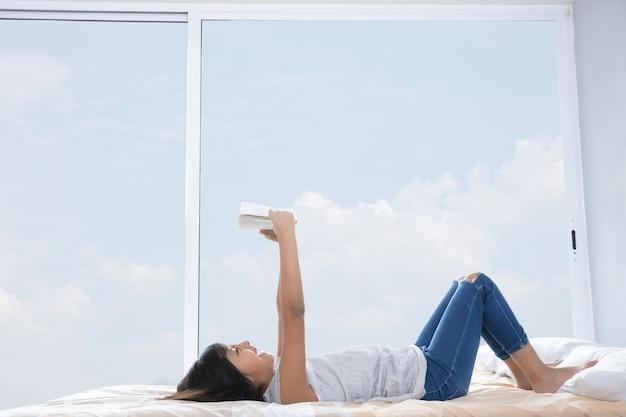 Jolie fille au lit, lisant un livre