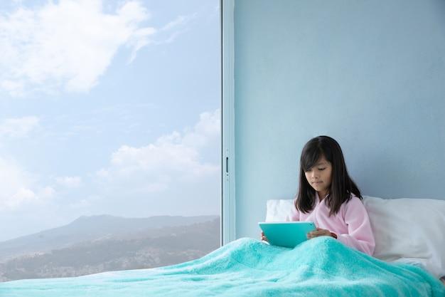 Jolie fille au lit avec tablette numérique