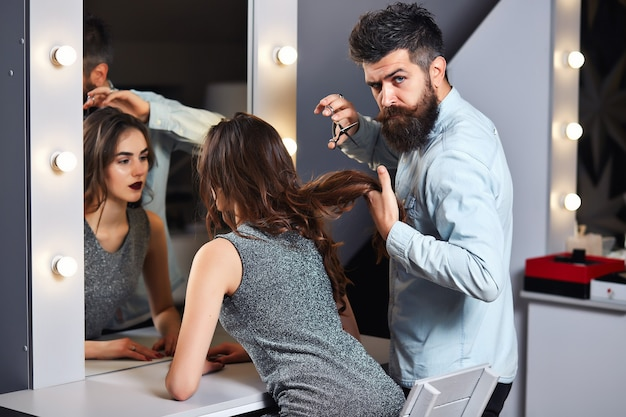 Jolie fille au salon de coiffure avec coiffeur masculin