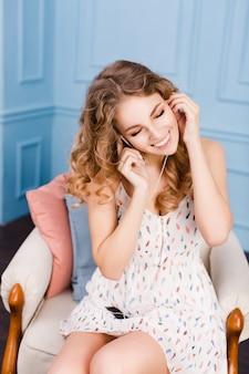Jolie fille aux cheveux blonds bouclés est assise sur un fauteuil en studio avec des murs bleus et des meubles bruns.
