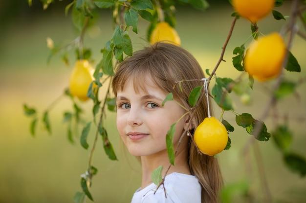 Une jolie fille aux cheveux blonds dans un t-shirt blanc avec des citrons d'été dans le jardin sous un arbre