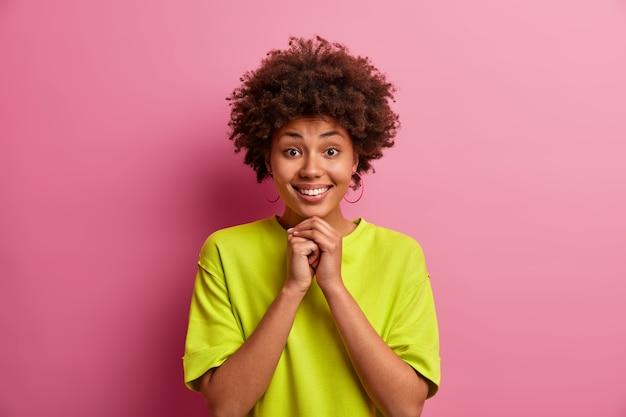Jolie fille aux cheveux bouclés, garde les mains sous le menton, sourit joyeusement, a les dents blanches, porte un t-shirt vert décontracté, pose