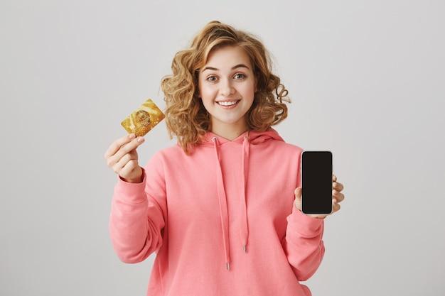 Jolie fille aux cheveux bouclés montrant une carte de crédit dorée et un écran de téléphone portable