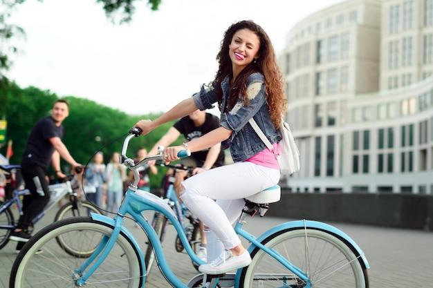 Jolie fille aux cheveux bouclés sur un vélo dans la ville
