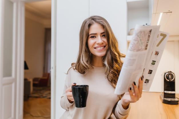Jolie fille aux cheveux brun clair tenant le magazine et riant dans sa chambre