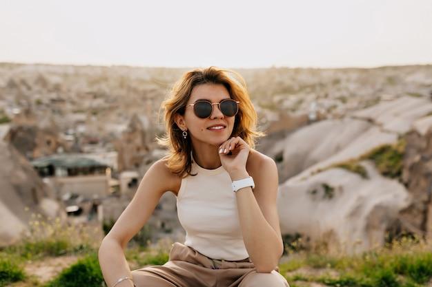 Jolie fille aux cheveux courts et clairs dans des lunettes de soleil souriant et regardant loin au soleil parmi les montagnes avec vue sur la ville