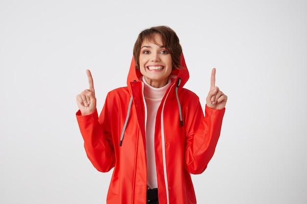 Jolie fille aux cheveux courts positive en manteau de pluie rouge, sourit largement, regarde, veut attirer votre attention sur l'espace de copie au-dessus de sa tête, pointe du doigt. permanent.