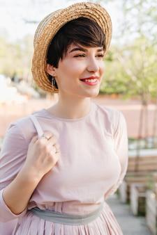 Jolie fille aux cheveux courts rêveur souriant, regardant ailleurs pendant la promenade dans le parc