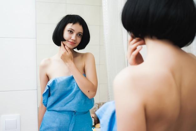 Jolie fille aux cheveux courts se regarde dans le miroir