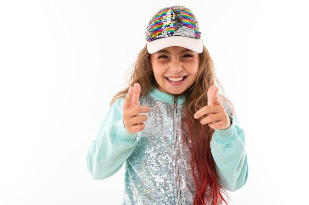 Jolie fille aux cheveux longs avec un costume de sport décontracté et une casquette de baseball montre une classe à la caméra sur un fond blanc
