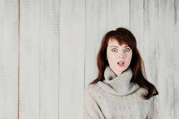 Jolie fille aux cheveux longs dans un pull gris, de grands yeux surpris, la bouche ouverte