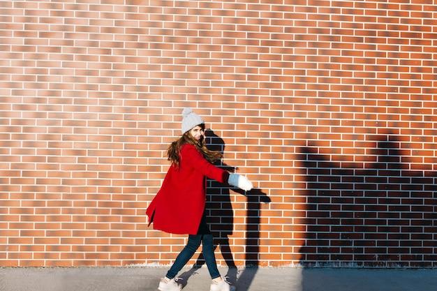 Jolie fille aux cheveux longs en manteau rouge et bonnet tricoté sur le mur extérieur. elle se retourne et sourit.