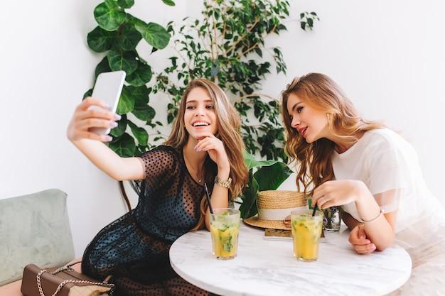 Jolie fille aux cheveux longs en robe élégante faisant selfie avec un ami tout en se détendant dans un restaurant confortable