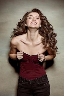 Jolie fille aux cheveux longs, souriant et profitant de la vie