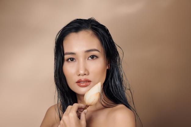 Jolie fille aux cheveux longs souriante et tenant des boutons de lotus séchés sur fond beige.