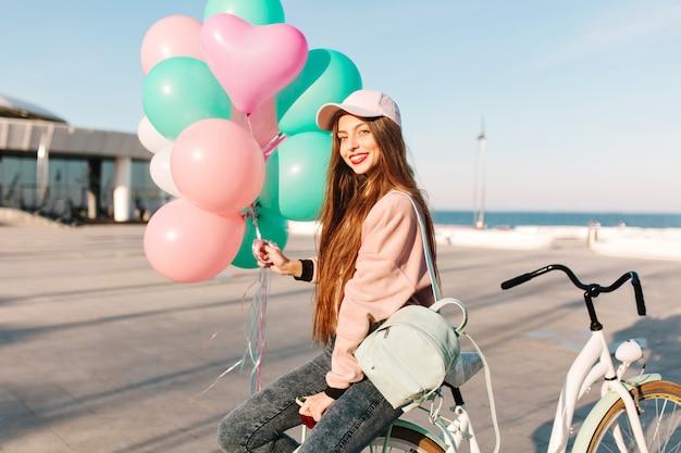 Jolie fille aux cheveux longs en tenue rose, assise sur le vélo avec des ballons en attente d'un ami de voyage.