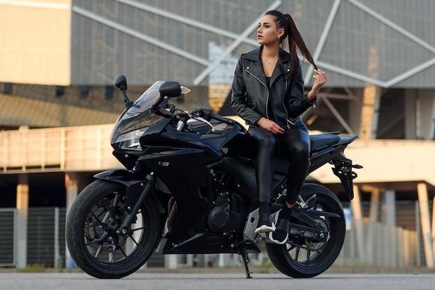 Jolie fille aux cheveux longs en veste de cuir noir et pantalon sur un parking extérieur avec une moto de sport élégante au coucher du soleil.