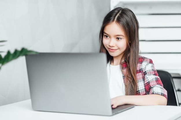 Jolie fille aux cheveux noirs aux yeux noirs tout en étant assise sur un ordinateur portable la table à la maison