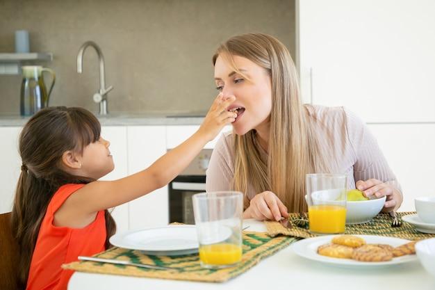 Jolie fille aux cheveux noirs donnant un cookie à sa mère pour la dégustation et la morsure, prenant le petit déjeuner avec sa famille