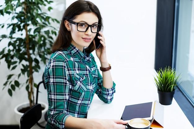 Jolie fille aux cheveux noirs portant chemise et lunettes assis dans un café avec tablette et tasse de café, parler au téléphone mobile, concept indépendant, regardant la caméra.