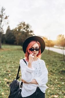Jolie fille aux cheveux rouges et chapeau relaxant dans le parc, temps d'automne.