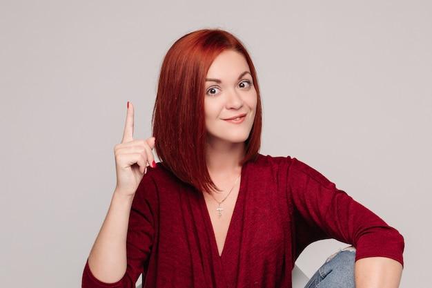 Jolie fille aux cheveux rouges en chemisier bordo et jeans pense à quelque chose.