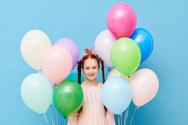 Jolie fille aux cheveux rouges tenant des ballons