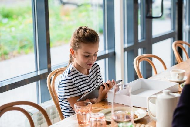 Une jolie fille aux cheveux tressés est assise à une table avec une tablette.
