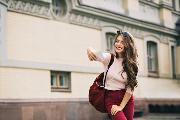 Jolie fille aux lèvres vineuses et aux cheveux longs fait un selfie-portrait en ville. elle porte un pantalon vineux, un sac. elle a l'air excitée.