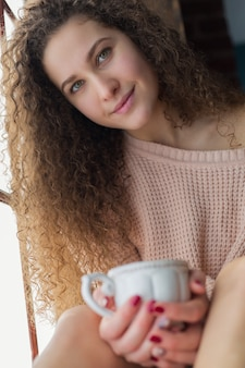 Jolie fille aux longs cheveux bouclés assise sur un rebord de fenêtre. une fille tenant une tasse blanche dans ses mains.