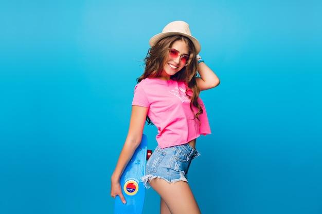 Jolie fille aux longs cheveux bouclés en chapeau posant sur fond bleu en studio. elle porte un short, un t-shirt rose, des lunettes de soleil roses. elle tient une planche à roulettes bleue sur le butin et sourit à la caméra.