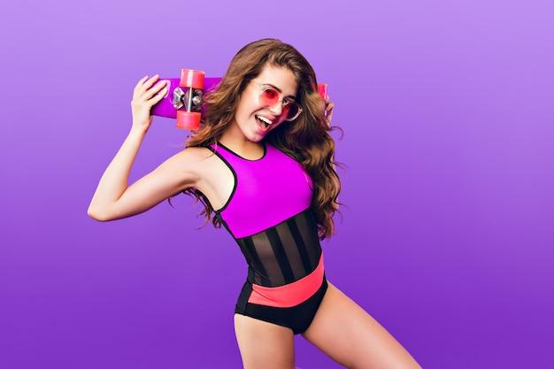 Jolie fille aux longs cheveux bouclés dans des lunettes de soleil roses sur fond violet en studio. elle porte un maillot de bain et tient une planche à roulettes rose sur les épaules.