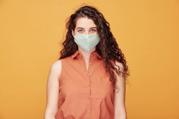 Jolie fille aux longs cheveux ondulés noirs portant un masque de protection contre l'infection à coronavirus