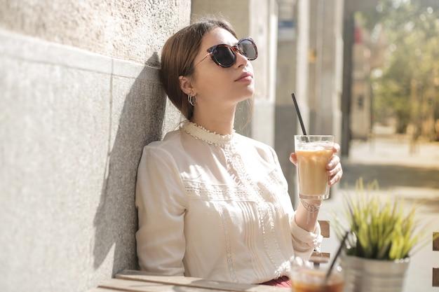 Jolie fille ayant un café glacé
