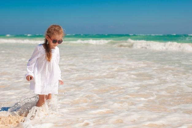 Jolie fille de bambin en robe blanche, debout dans l'eau peu profonde à la plage exotique