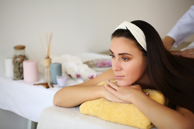 Jolie fille bénéficiant d'un massage du visage dans un spa