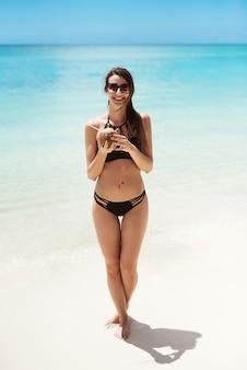 Jolie fille en bikini tenant la noix de coco, se faire bronzer sur la belle plage