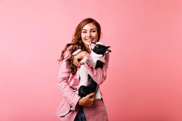 Jolie fille blanche tenant le bulldog et riant. blithesome femme caucasienne avec chien s'amusant.