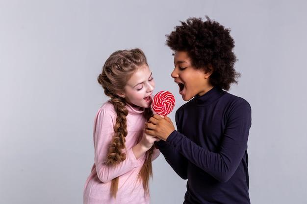 Jolie fille blonde. actif rayonnant des enfants opposés mordant un bonbon ensemble tout en se battant de manière ludique pour lui