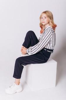 Jolie fille blonde adorable caucasienne en uniforme scolaire sur fond blanc