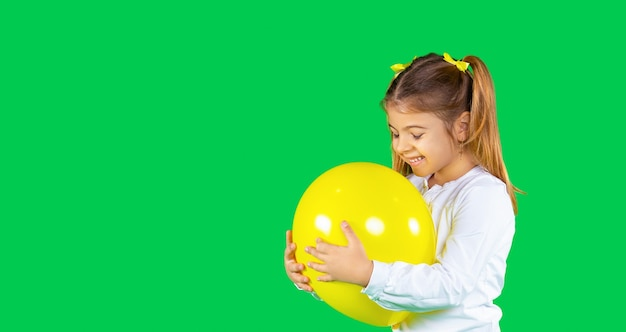 Jolie fille blonde d'âge préscolaire avec deux nattes embrasse un ballon de couleur éclairant