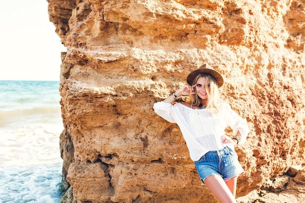 Jolie fille blonde aux cheveux longs pose à la caméra sur la plage sur fond de pierre. elle sourit.